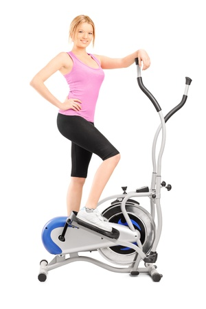 crosstrainer: Full length portrait of a young woman posing on a cross trainer fitness machine, isolated on white background