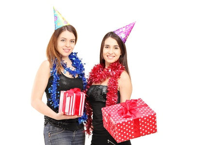Two female friends standing close together and holding gifts at party isolated on white background photo