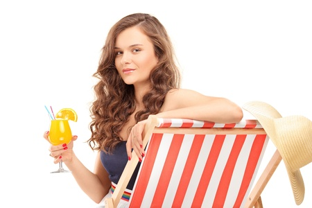 Young female sitting on a sun lounger and drinking a cocktail, isolated on white background photo