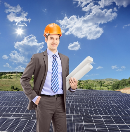 Architect wearing helmet and holding blueprints, with solar photovoltaic cell panels in the background, shot with a tilt and shift lens photo