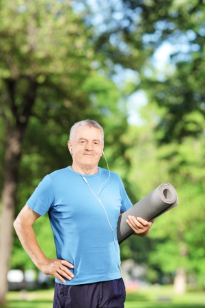 Mature man holding an exercising mat and posing in park photo