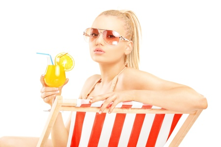 Attractive blond female sitting on a sun lounger and drinking a cocktail, isolated on white background photo