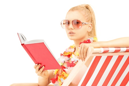 Attractive blond female sitting on a sun lounger and reading a book, isolated on white background photo