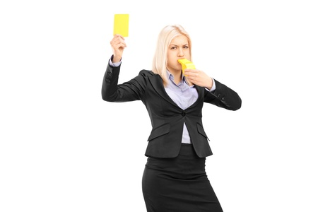 Angry businesswoman blowing a whistle and showing a yellow card, isolated on white background photo