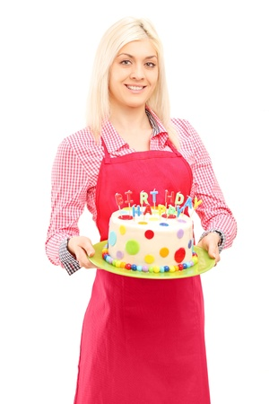 Blond female chef in apron holding a delicious cake with happy birthday candles, isolated on white background   photo