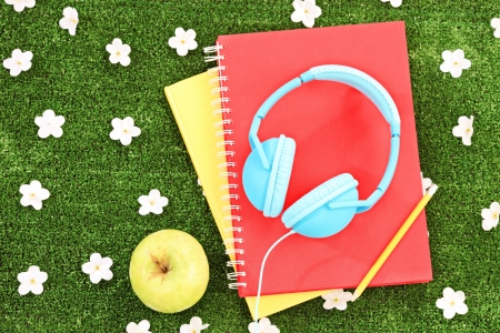 music book: Books, headphones and apple on a green grass with daisy flowers Stock Photo