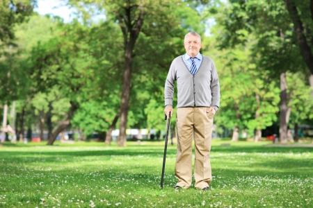 Full length portrait of a senior man walking with a cane in a park photo