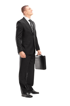 Full length portrait of a young businessman with briefcase looking upwards isolated on white background   photo