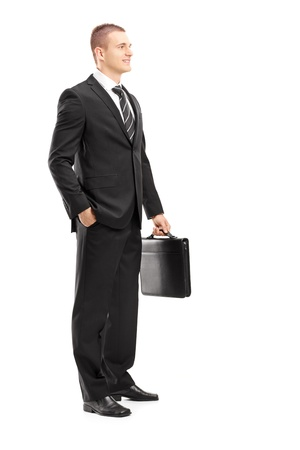 Full length portrait of a young businessman with briefcase posing isolated on white background   photo