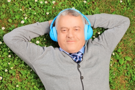 Mature man lying on green grass with headphones, listening to music photo