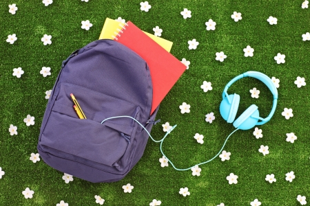 pocket book: School backpack with books and headphones on a green grass with daisy flowers