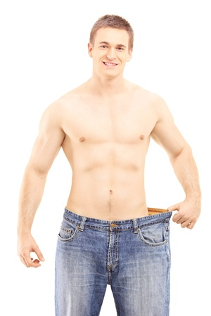 Shirtless smiling male showing his lost weight by putting on an old jeans, isolated on white background   photo