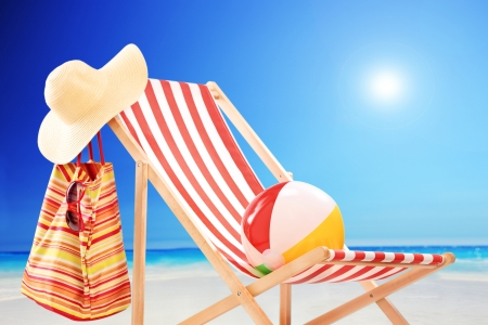 deck chair: Beach chair with ball, bag and hat at sunny day by the sea