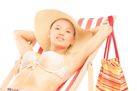 Beautiful smiling female in bikini enjoying on a beach chair isolated on white background photo