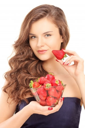 Beautiful young woman holding a bowl of strawberries isolated on white background photo