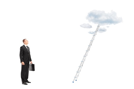 reachability: Full length portrait of a young businessman standing in front of a ladder with clouds looking upwards, isolated on white background Stock Photo
