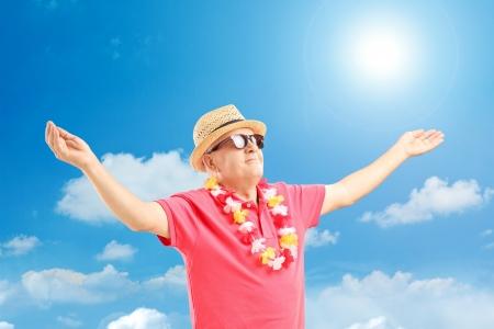 felicidad: Hombre maduro feliz en vacaciones abriendo los brazos en un día soleado
