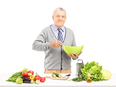 Smiling gentleman prepairing meal with fresh vegetables isolated on white background  photo