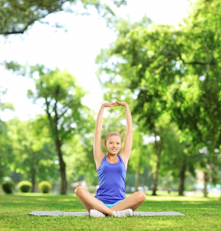 Young woman exercising in a park on a sunny day, shot with a tilt and shift lens photo