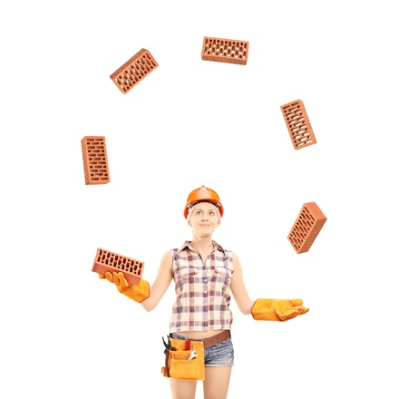juggling: Female construction worker juggling bricks isolated on white background Stock Photo