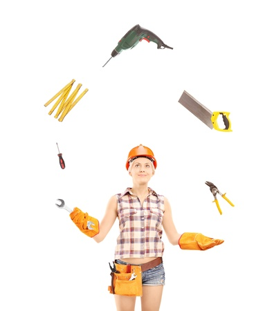 Female manual worker juggling with tools, isolated on white background photo