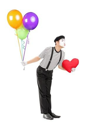 mimic: Full length portrait of a young mime artist with balloons and red heart giving kisses isolated on white background