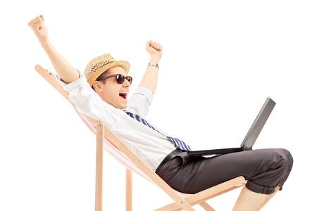 白い背景で隔離されたビーチの椅子に座ってのラップトップで興奮して男