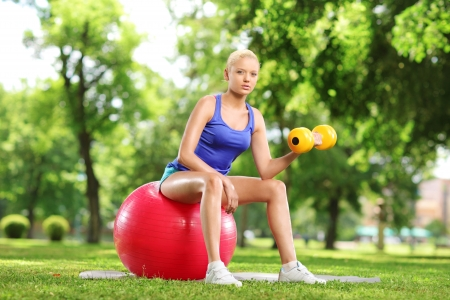 Female lifting weigth and sitting on an exercise ball in a park photo