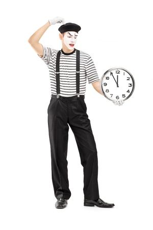 mimic: Full length portrait of a mimic holding a clock and thinking, isolated on white background