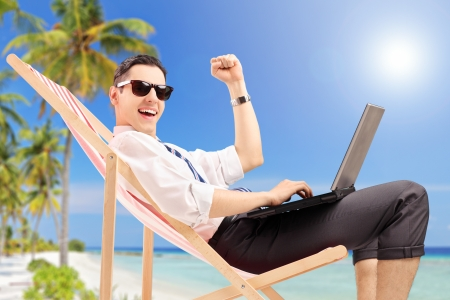 freedom concept: Happy businessman with a laptop on a tropical beach
