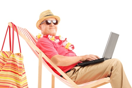 Mature male tourist on a sun lounger with a laptop, isolated on white background photo
