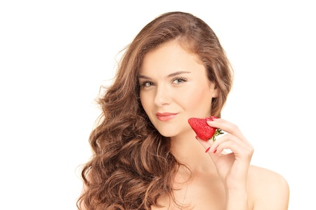 Pretty brunette woman holding a strawberry, isolated on white background photo
