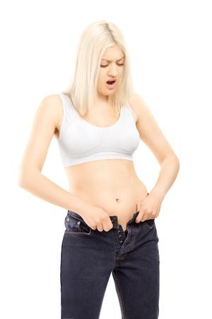 vientre femenino: Mujer que intenta meterse en viejo par de pantalones vaqueros, aislados en fondo blanco