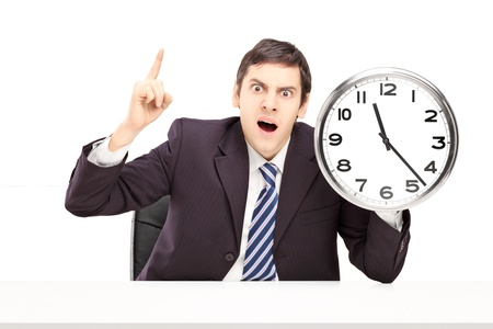 Angry businessman holding a clock, isolated on white background photo