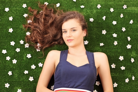 Beautiful young female lying on a green grass with daisy flowers photo