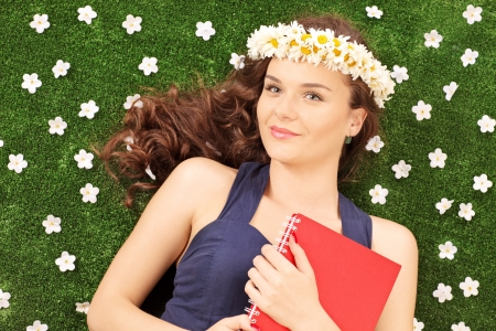 Beautiful young woman with a daisy hair wreath lying on a green grass with daisy flowers photo