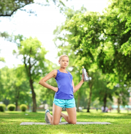 female athlete: Female athlete holding a water bottle and resting after excericise, in a park, shot with a tilt and shift lens