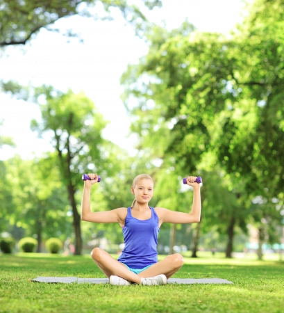 Female in a park sitting on a mat and exercising with dumbbells, shot with a tilt and shift lens photo