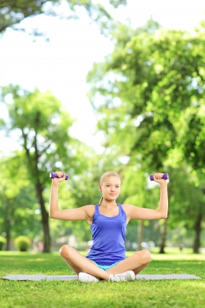 Female in a park sitting on a mat and exercising with dumbbells photo