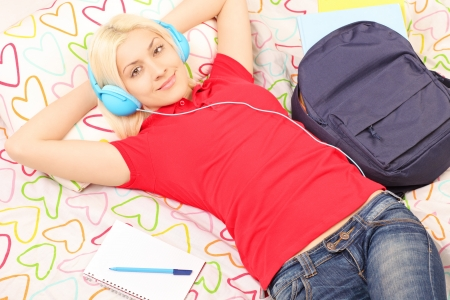 Female student lying in bed with backpack and notebook and listening to music Stock Photo - 20396537