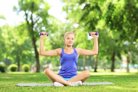 Female exercising with dumbbells in a park photo