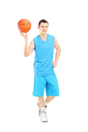Full length portrait of a basketball player holding a basketball and posing isolated on white background photo