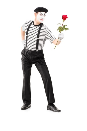 Full length portrait of a mime asrtist giving a rose flower isolated on white background photo