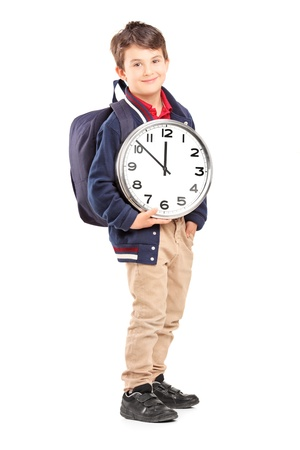 Full length portrait of a school boy with backpack holding a wall clock and looking at camera, isolated on white background photo