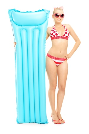 Full length portrait of a young woman in bikini holding a swimming mattress isolated against white background photo