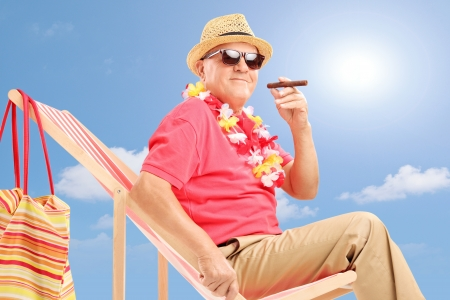 Gentleman smoking a cigar and enjoying on a beach chair on a sunny day photo