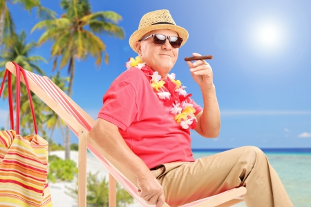 Gentleman smoking a cigar and enjoying on a sun lounger on a tropical beach next to a sea and palm trees photo
