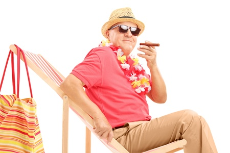 Gentleman smoking a cigar and enjoying on a sun lounger, isolated on white background photo