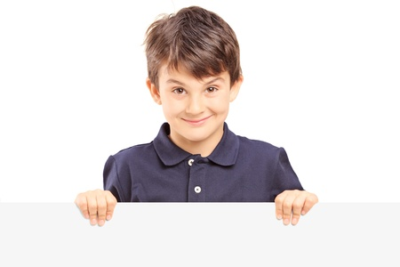 Little smiling boy standing behind a blank panel isolated against white background Stock Photo - 20396245
