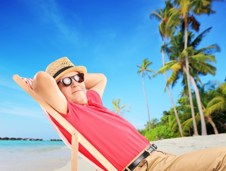 Mature male tourist enjoying on a tropical beach next to a sea and palm trees photo